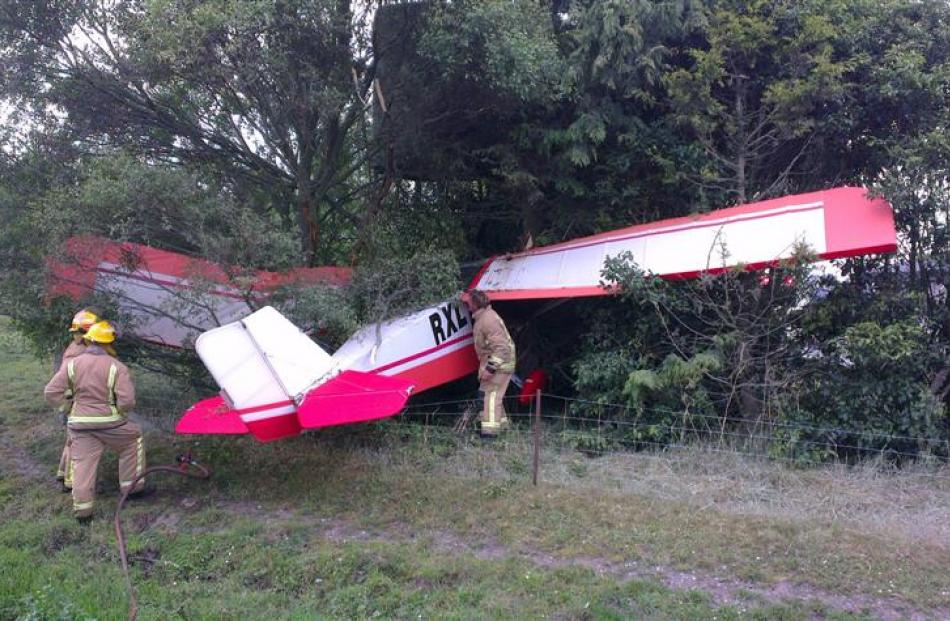 Emergency services keep a watch on fuel leaking from the microlight that crashed into trees at...