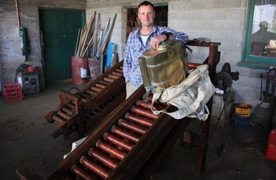 Simon Webb with equipment once used on the orchard including an old brass spraying knapsack, an...