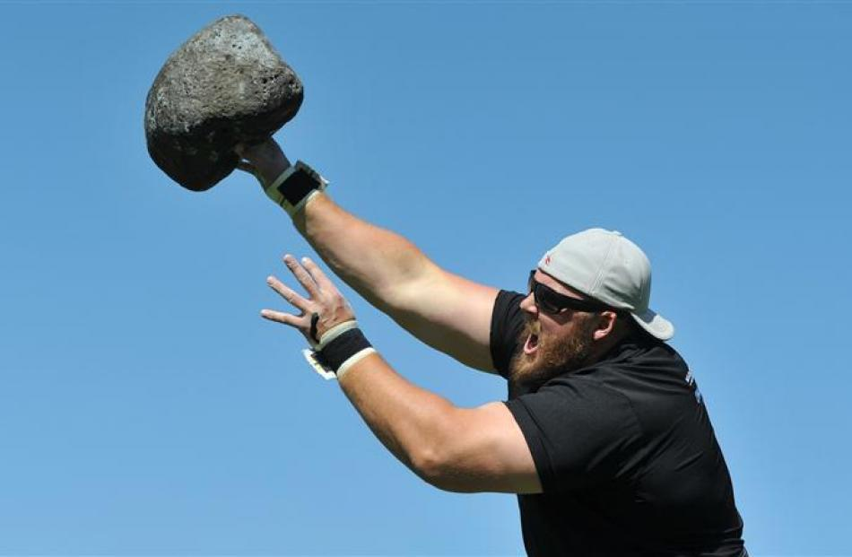 Luke Reynolds, from Australia, puts the stone in the Highland games.
