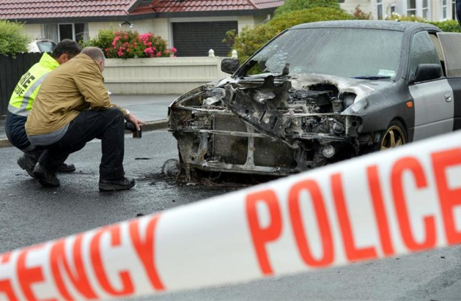 Fire and police staff examine a burnt-out car in Mavis St, St Clair.