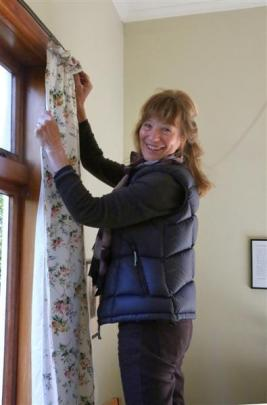 Janet Frame Eden Street Trust chairwoman Carol Berry makes alterations to curtains in Frame's old...