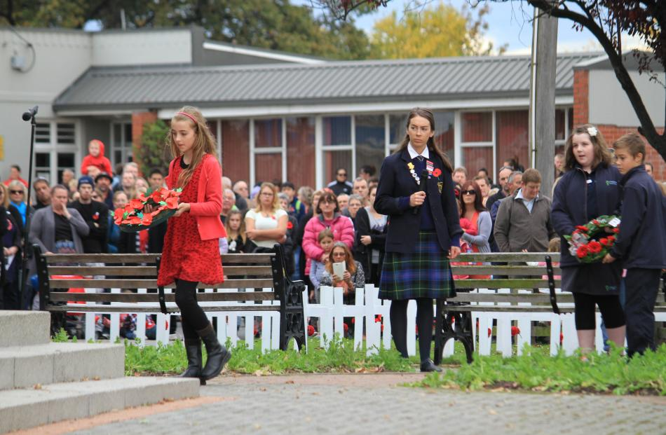 oe McElrea (9) lays a wreath at the Milton cenotaph for the Milton Public Library during Milton's...