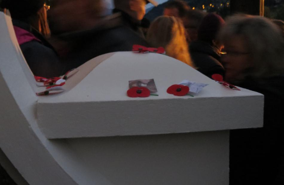 People pass by some of the poppies laid on the Queenstown Memorial Gates following the dawn...