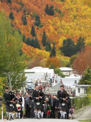 Pipers lead thousands of people from the Athenaeum Hall in Arrowtown to the war memorial.
