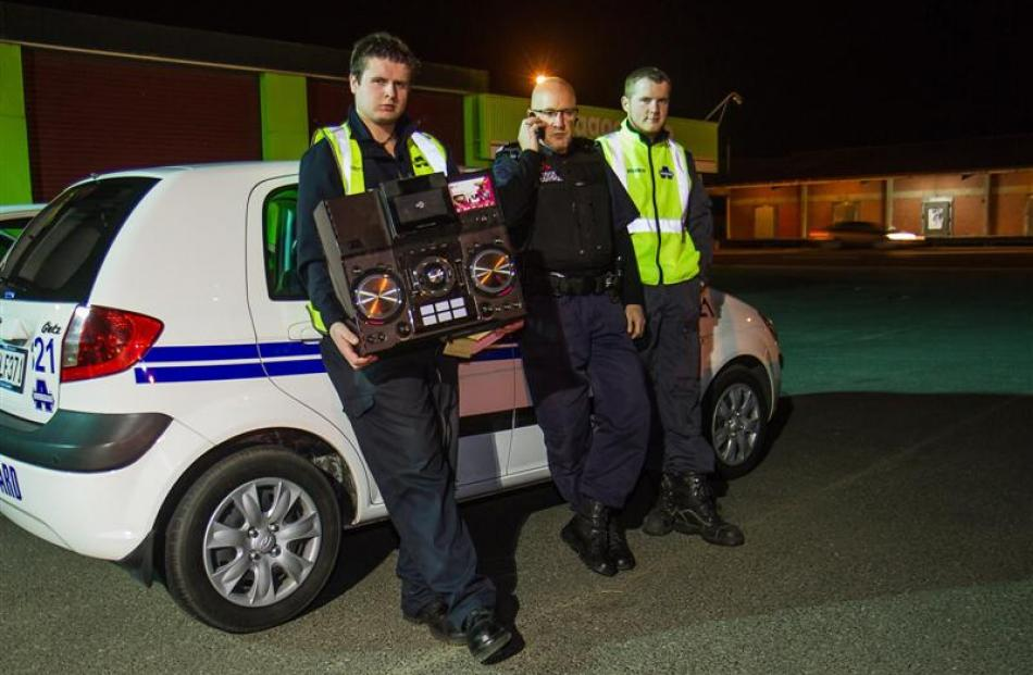 The officers with a confiscated stereo system outside  the Armourguard offices.