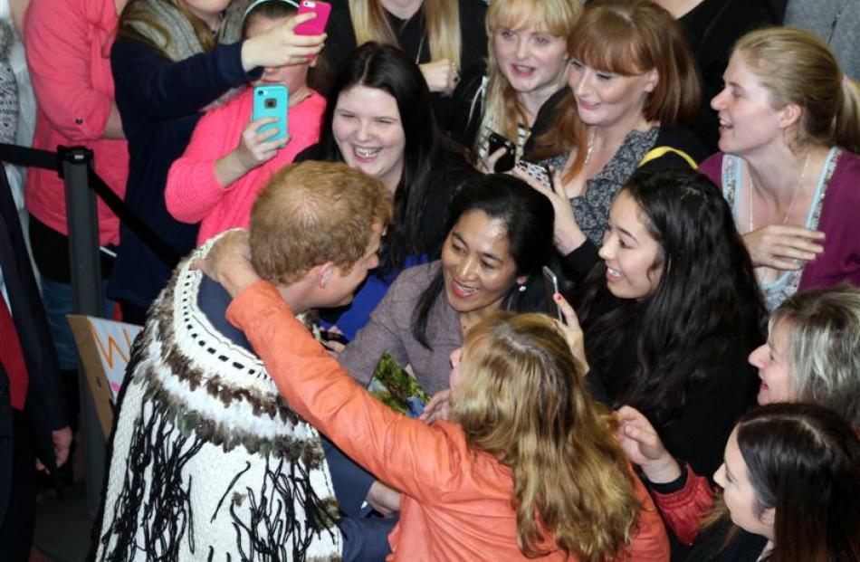 Prince Harry greets the crowd at Invercargill Airport as   Yvonne Gawn, of Invercargill, steals a...