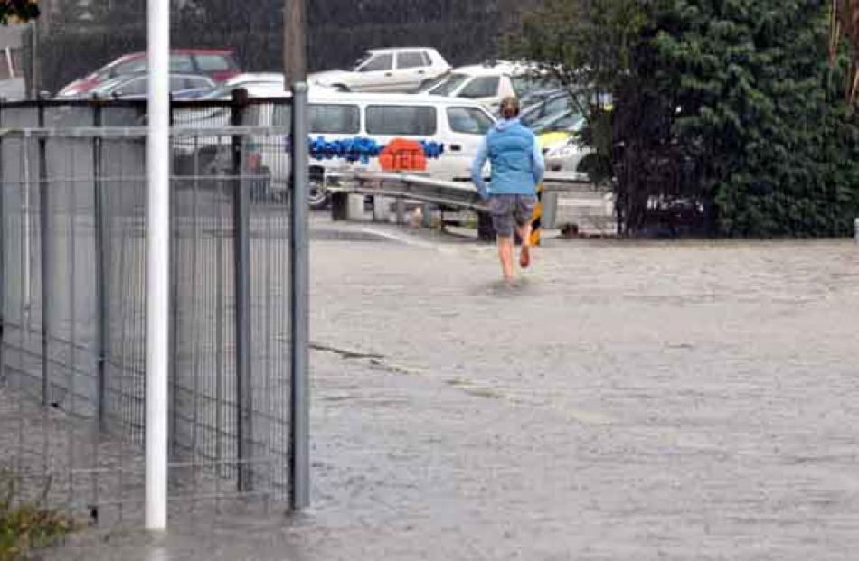 A woman runs through flooding towards East Taieri School.