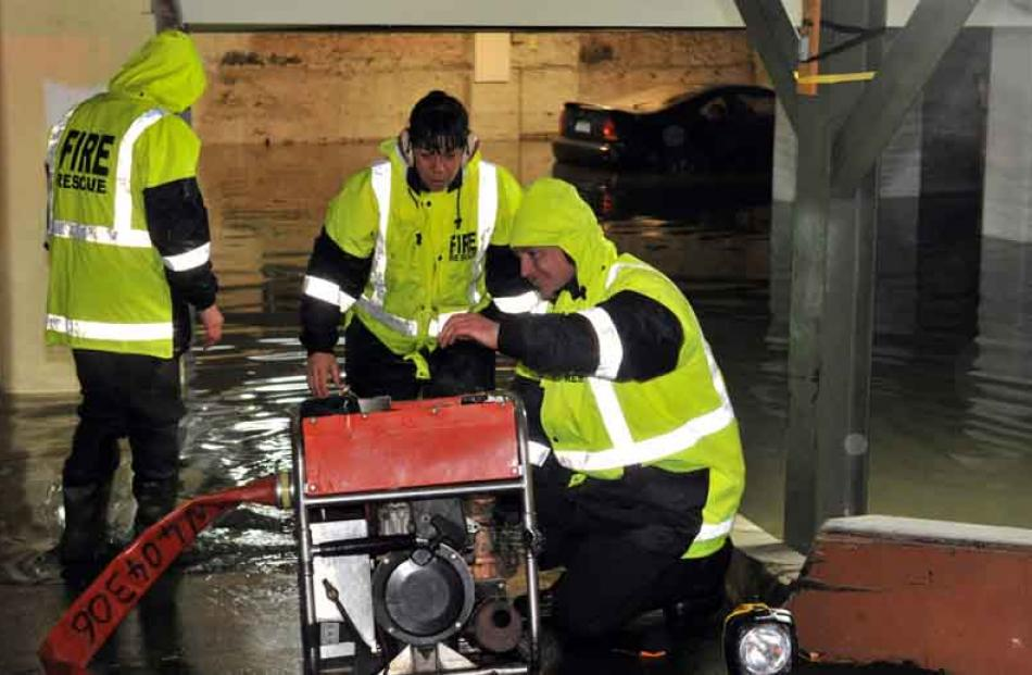 Firefighters set up a pump in a flooded basement, Crawford St.