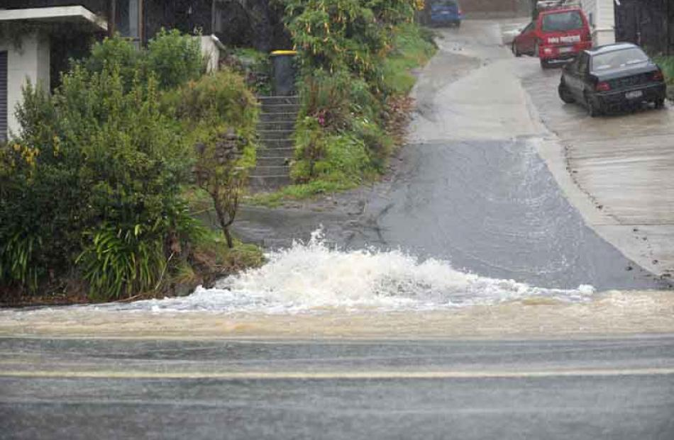 Water pours down a Forbury Rd driveway.
