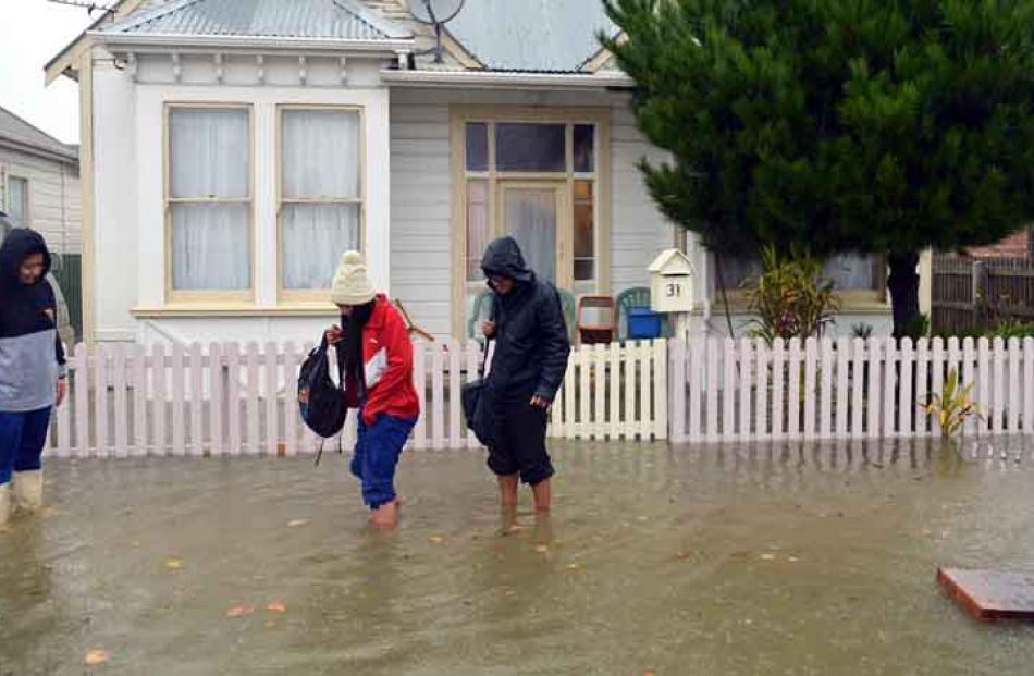 Darcel, Chantelle and Felix Pese evacuate their Nicholson St house as floodwaters rise.