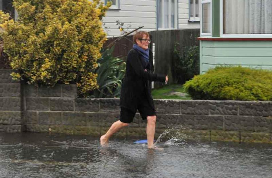 Pauline Osborne runs barefooted through the flood waters in Grove St, St Kilda.