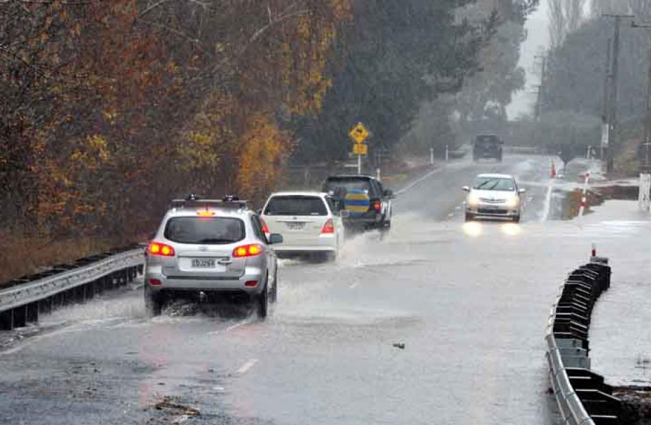 Cars negotiate flooding at the bottom of Three Mile Hill.
