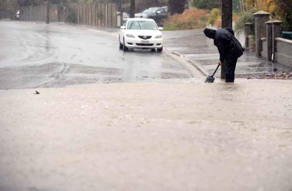 A Green Island resident cleans a drain.
