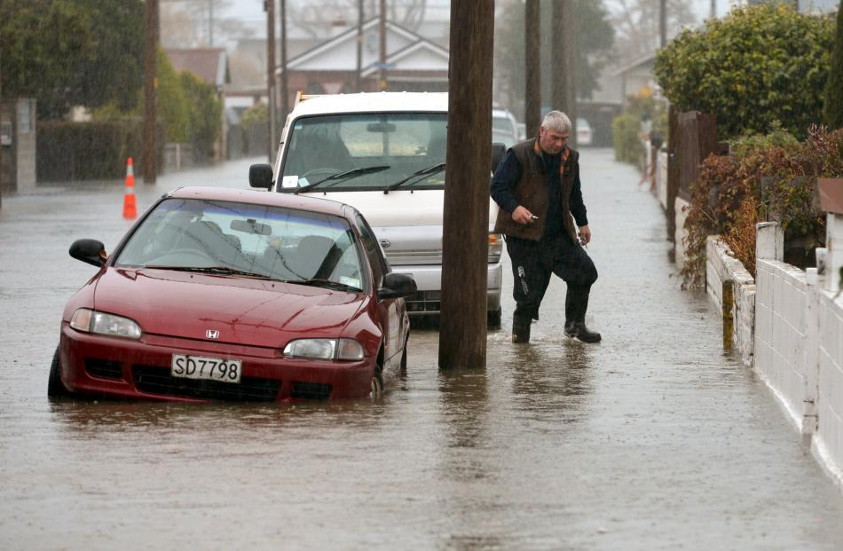 A resident in Nelson St, South Dunedin, heads to check flooding at his property.PHOTO: STEPHEN...