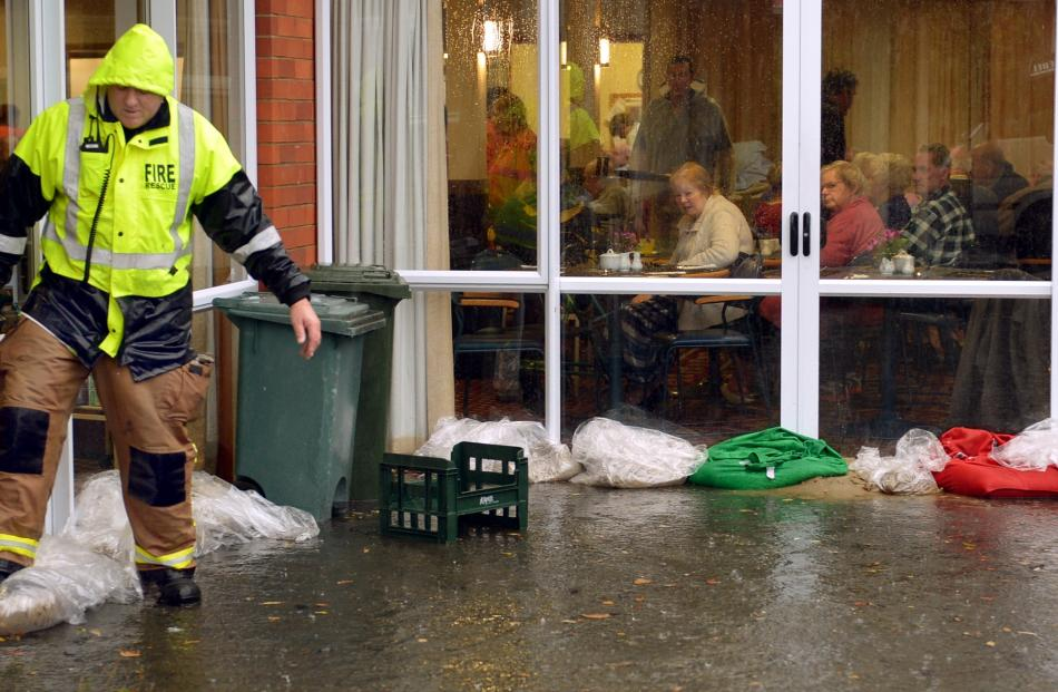Residents at Fulton home have lunch while a firefighter checks sand bags outside the dining room...