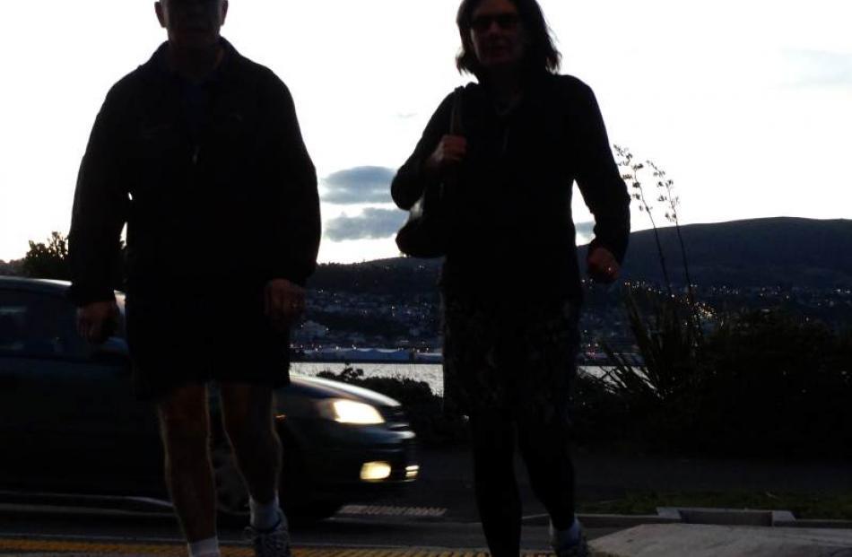 Two pedestrians hurry across Portobello Rd as night falls on Dunedin.
