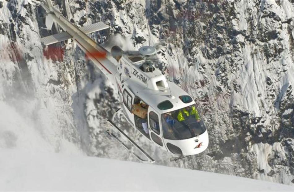 A helicopter being used to drop bombs to trigger avalanches.