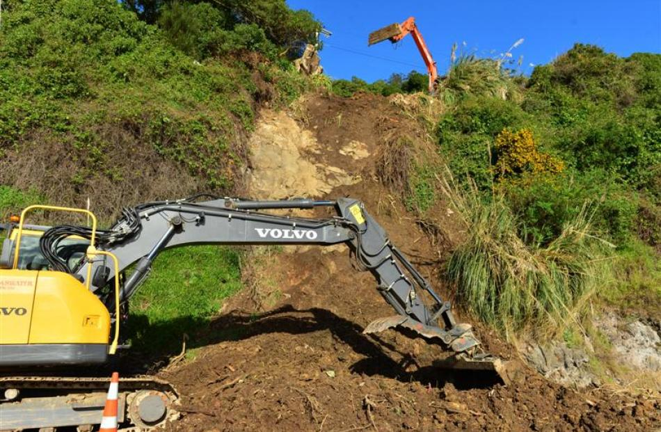Excavators clear debris from above Portobello Rd after a slip below the Hawkins' home in 2013....
