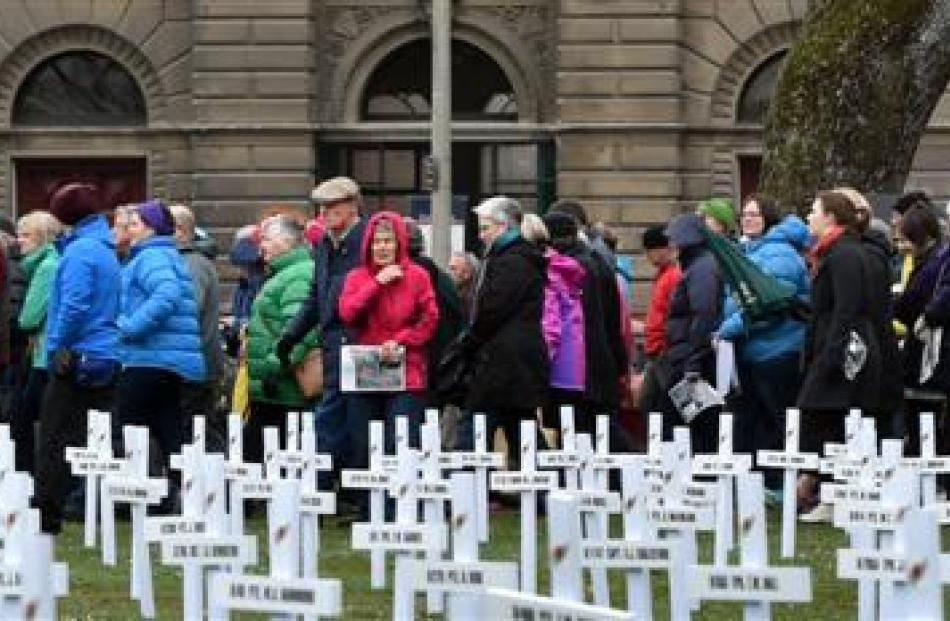 People taking part in the Dunedin Heritage Festival walk past the 693 crosses in Queens Gardens...
