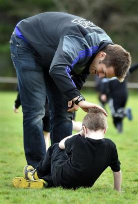 All Black captain Richie McCaw checks on Mataura School pupil Dion Woodrow (6) yesterday during a...