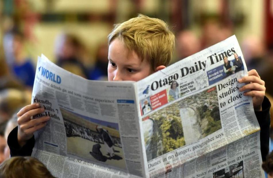 Andersons Bay School pupil Lachie Allibone (10) reads a newspaper at the  current events quiz for...