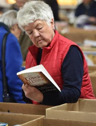 Avis Wilkes, of Mosgiel, learns more about a book on offer at the book sale.