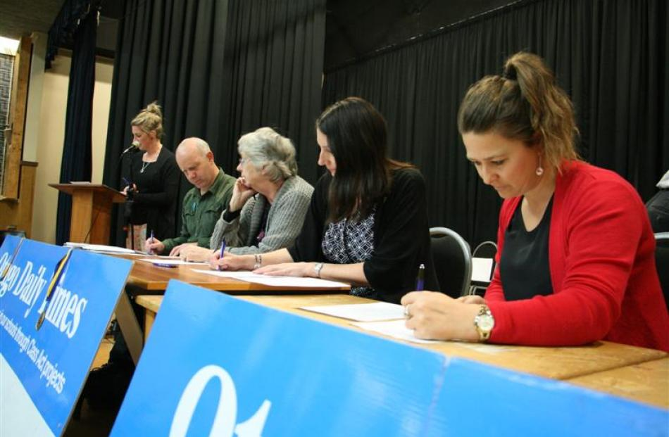 Quiz master Tineke Hayes, of Dunstan High School, reads out questions as teachers (from left) ...
