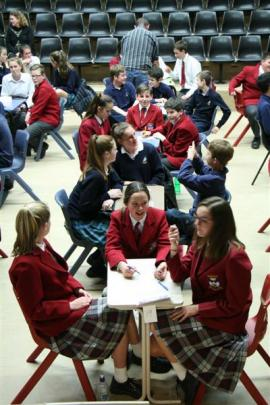 School pupils answer questions for spot prizes while quiz scores are tallied.