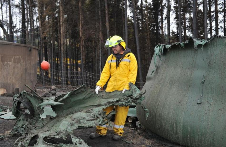 Firefighter Rayel Newman, of Brighton, holds part of a melted water tank on a property in...