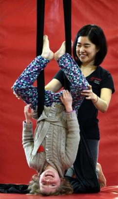 Georgia Hourigan (8),  helped by Brophy Aerial Studios' May Pilanthananond, finds herself on her...