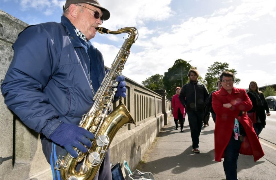 Concert-goers pass a busker while on their way to Forsyth Barr Stadium in Dunedin for Fleetwood...