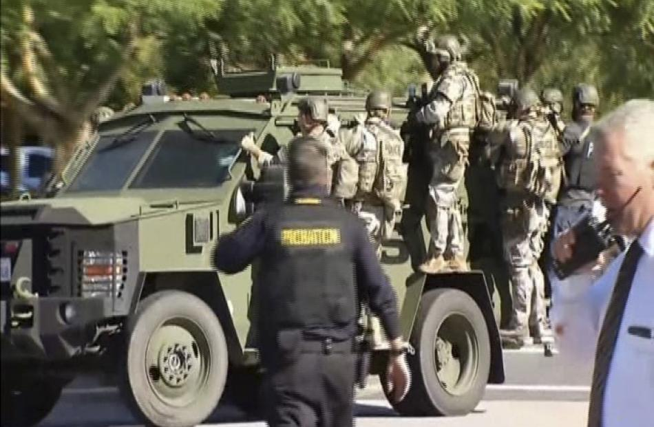 Police SWAT team members ride on an armoured vehicle outside the Inland Regional Center.