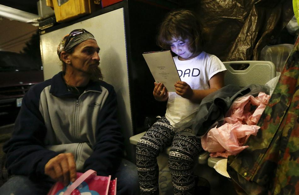 Emma Savage, 6, opens a birthday card given to her by her dad Robert Rowe, 42, a day labourer who...