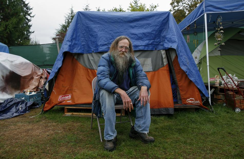 Lantz Rowland, 59 poses in front of his tent at SHARE/WHEEL Tent City 3 outside Seattle, Washington.