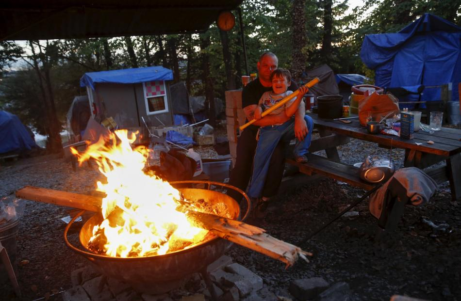 Matt Hannahs, 32, poses with his son Devin outside their tent by a wood fire at Nickelsville...