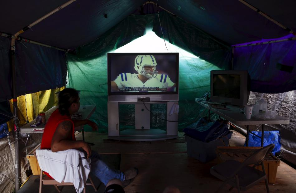 Tent city residents watch an NFL football game in their communal television area at SHARE/WHEEL...