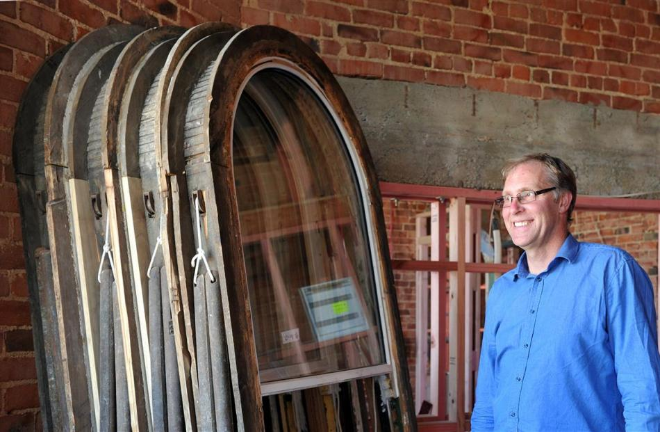 Building owner Stephen Macknight and a collection of 135-year old window frames fitted with new...
