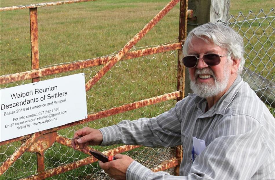 Waipori historian David Still attaches a reunion notice to the Waipori Cemetery gate.