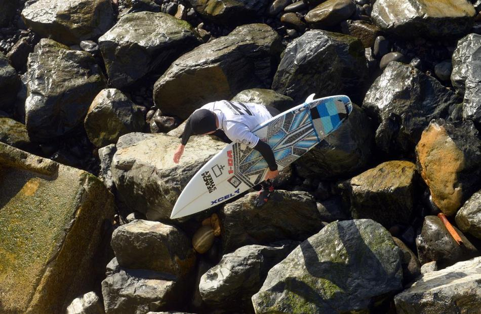 Taranaki surfer Jarred Hancox tackles the surf and  braves  the rocks on St Clair Beach during...