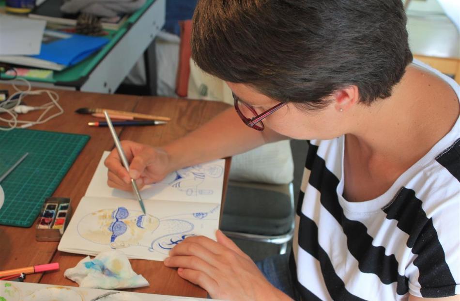 Marcelilla Pilla paints a cafe customer.