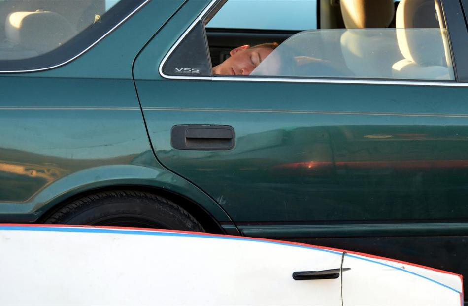 A camper sleeps in his car in the reserve early yesterday.