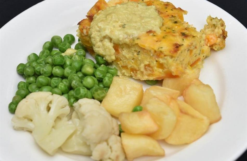 Pumpkin and cheese gratin with potatoes, cauliflower and peas.