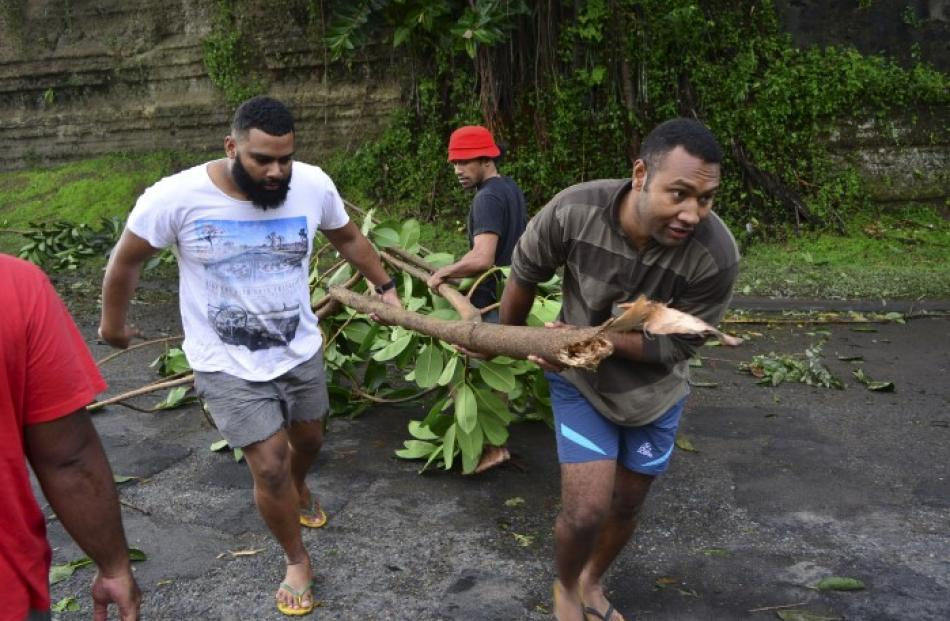Men clear a road of a fallen tree in Suva. Photo: Reuters