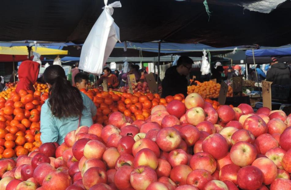 Stacks of persimmons and apples at the huge Otara market in South Auckland.