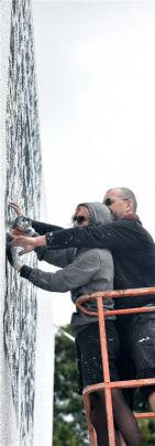 Polish street artist NeSpoon (left) and her husband Martin Rutkiewicz begin their lacework mural...