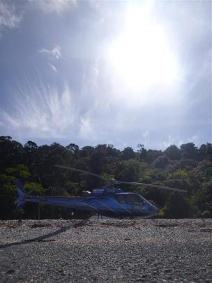 The helicopter touches down on the narrow strip of beach.