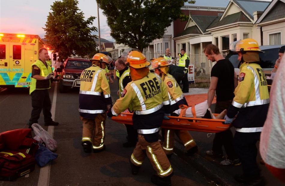 Emergency services carry an injured person to an ambulance. Photo: Gregor Richardson