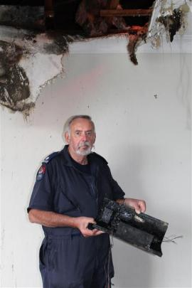 Fire investigator Mike Cahill holds one of the neon light transformers which he believes may have...