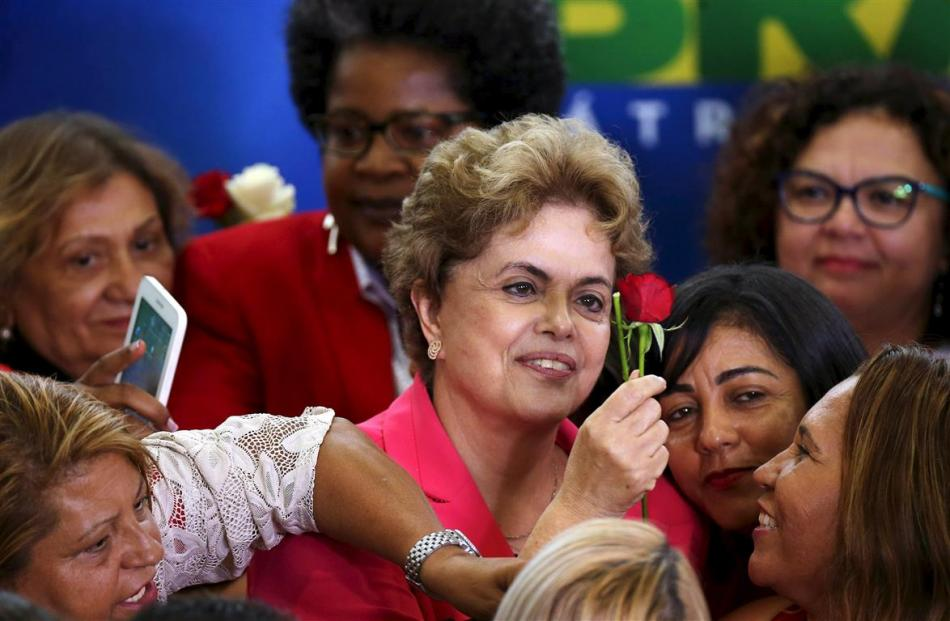 Mrs Rousseff raises a rose during the meeting ''Women in Defence of Democracy''  in Brasilia last...