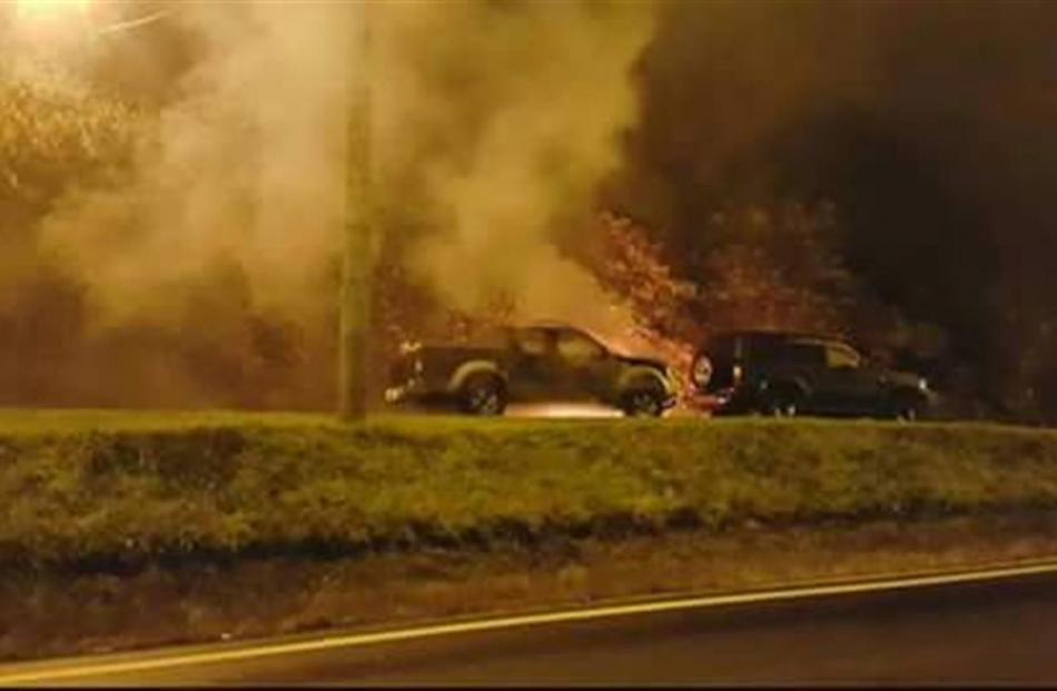 Phil and Richard Warrington's vehicles burn outside their Maia home on Saturday. PHOTO: SUPPLIED